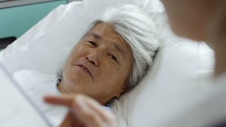 Medium shot of cheerful elderly Asian woman lying in hospital bed and talking with unrecognizable doctor making notes on clipboard during morning rounds
