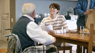 Medium shot of cheerful female social worker giving household bills sheet to senior man in wheelchair and explaining him something while unrecognizable male volunteer unpacking groceries