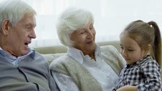 Medium shot of cheerful grandmother and grandfather chatting with cute preschool girl while babysitting