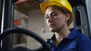 Medium shot of concentrated female worker wearing blue uniform and hard hat operating forklift in warehouse