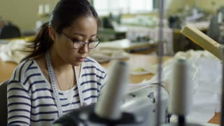 Medium shot of concentrated young Asian woman in glasses using sewing machine while working at tailoring shop, measuring tape hanging on her neck