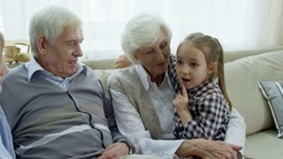 Medium shot of cute girl and boy sitting on sofa with grandparents and chatting