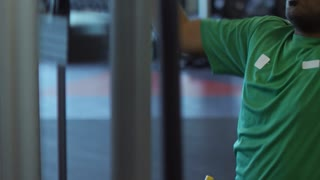Medium shot of determined Arab man doing front pull-downs on machine in gym and breathing hard