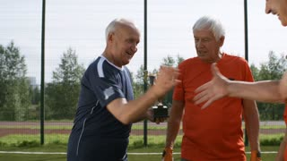 Medium shot of elderly man giving football cup to winning team and clapping hands while they are celebrating success
