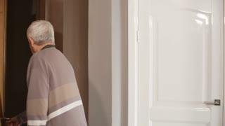Medium shot of elderly man opening door and greeting two grandchildren or volunteers and talking to them in friendly way