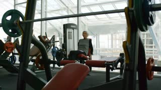 Medium shot of elderly woman in fitness clothes training on leg curl machine in gym