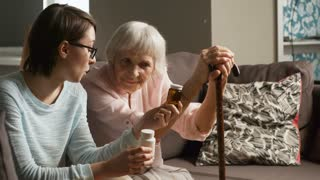 Medium shot of elderly woman sitting on sofa in living room and listening to granddaughter or caregiver, who is explaining doctor's prescription to her
