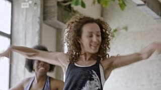 Medium shot of energetic young female teacher with curly hair teaching zumba dance moves to young women