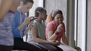 Medium shot of female African women sitting on windowsill and chatting with person off camera