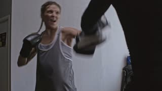 Medium shot of fierce young woman throwing kicks and punches at her sports instructor seen from his back, who is using boxing kick pads