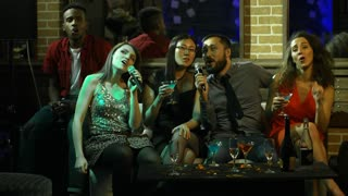 Medium shot of five multi ethnic young friends enjoying music when sitting on couch and singing karaoke at party in nightclub