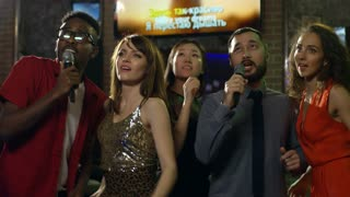 Medium shot of five young friends of different ethnicities standing in line when singing and dancing in karaoke bar, song lyrics shown on screen