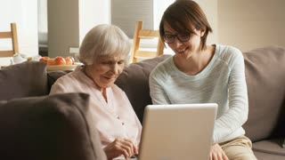 Medium shot of friendly female volunteer or granddaughter helping elderly lady and teaching her to use laptop computer