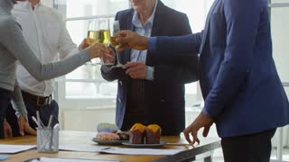 Medium shot of friendly office workers clinking glasses of champagne and clapping hands to say thank you to retiring colleague