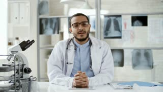 Medium shot of friendly young black doctor in lab coat and glasses sitting at desk in medical laboratory and explaining something to camera