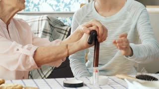 Medium shot of friendly young woman helping elderly lady get ready in the morning and applying makeup on her face