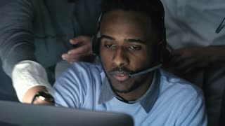 Medium shot of frustrated African man with headset working on computer and listening to people giving him advice