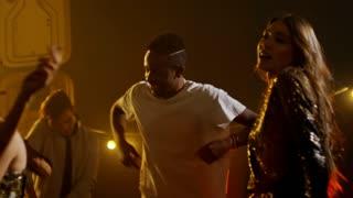 Medium shot of group of excited multi ethnic friends enjoying rhythmic music when partying in nightclub