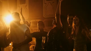 Medium shot of group of young multi ethnic friends dancing with hands in the air and drinking alcohol at party in nightclub lit by warm amber colored spotlight