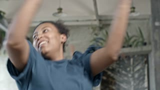 Medium shot of happy African woman dancing and doing aerobics in fitness class