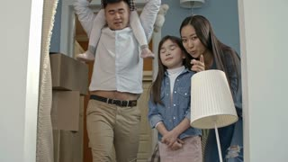 Medium shot of happy Asian family with children chatting and looking at interior of new house after moving