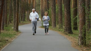 Medium shot of happy elderly man and woman smiling and running along pavement in park