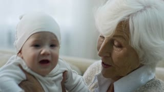 Medium shot of happy grandmother with grey hair holding fussy baby and taking dummy from unrecognizable grandfather