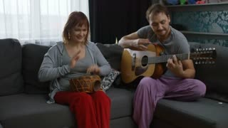 Medium shot of happy young woman and man playing guitar and ethnic drums and laughing