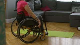 Medium shot of independent paraplegic woman getting out of wheelchair and sitting down on yoga mat