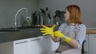 Medium shot of independent woman in wheelchair turning on water faucet in kitchen and washing dishes