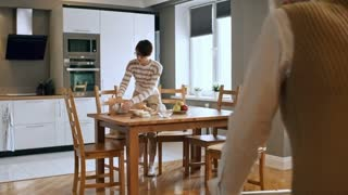 Medium shot of infirm elderly lady with walkers walking towards kitchen table and sitting down with help of young female carer preparing breakfast