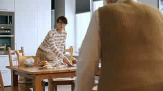 Medium shot of infirm elderly woman with walkers walking towards kitchen table, then sitting down with help of young female carer serving her breakfast
