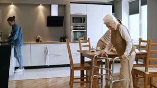 Medium shot of infirm senior lady with walkers leaving kitchen while young female caregiver cleaning kitchen table and male volunteer washing dishes