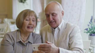 Medium shot of laughing senior woman and elderly man taking selfie and pulling funny faces while having date in cafe