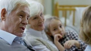 Medium shot of loving grandparents talking with grandson while babysitting; elementary age girl sitting on laps of grandmother