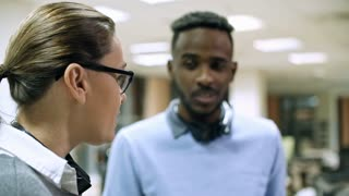 Medium shot of male African helpdesk worker with headset laughing while listening to female colleague telling story