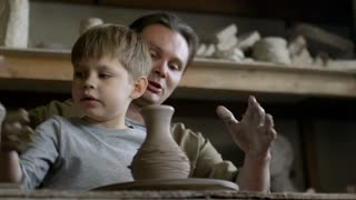 Medium shot of male artisan helping cute little boy throwing vase on spinning pottery wheel in ceramics class