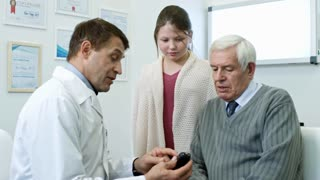 Medium shot of male doctor in lab coat showing glucose meter to senior man and schoolgirl and explaining how to use it