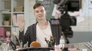 Medium shot of male teenage beauty guru shooting makeup tutorial: he waving hello before camera on tripod, then showing how to cleanse face with micellar water