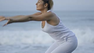 Medium shot of mature woman in white doing yoga on beach: she performing raised arms pose, then transitioning to forward bend