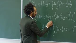 Medium shot of middle-aged teacher of mathematics standing at blackboard with equations written on it and explaining topic to students during lecture at university