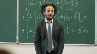Medium shot of middle eastern man with curly hair standing at blackboard with equations written on it and explaining topic to students