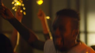 Medium shot of overjoyed black man in white t-shirt jumping with sparkler in hand during party with friends