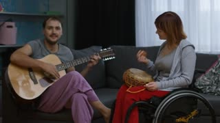 Medium shot of paraplegic happy woman in wheelchair snapping fingers and moving shaker instrument to rhythm as cheerful bearded man plying guitar and singing