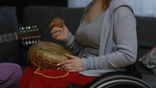 Medium shot of paraplegic woman in wheelchair using moving shaker instrument to rhythm of bearded man plying guitar and singing song