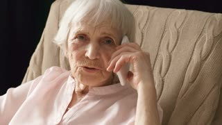 Medium shot of retired Caucasian woman sitting in rocking chair and looking at camera while having phone conversation