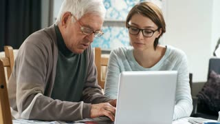 Medium shot of retired man in glasses sitting at kitchen table and learning to use laptop computer, his granddaughter or volunteer sitting next to him and helping him
