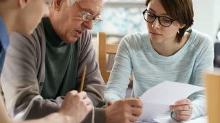 Medium shot of retired man in glasses trying to understand household bills and talking to two caregivers sitting next to him