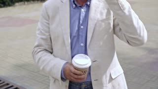 Medium shot of retired man in hat and glasses talking on the phone and drinking coffee from take away mug when walking in city