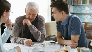 Medium shot of retired man sitting at table and telling something to two young caregivers or grandchildren